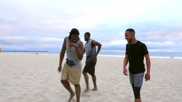 ms smiling friends hanging out after touch football game on beach - touch football video stock e b–roll