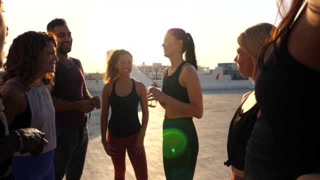 ms smiling friends in discussion after rooftop yoga class - vest stock videos & royalty-free footage