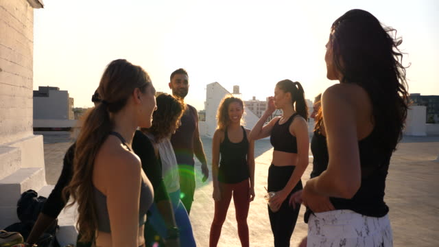 ms pan smiling friends in discussion after rooftop yoga class - vest stock videos & royalty-free footage