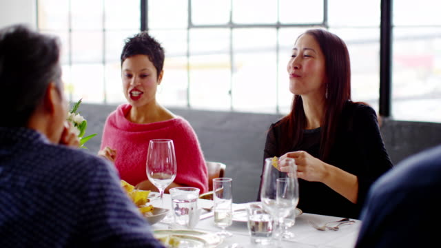 MS smiling friends in discussion at table during dinner party in loft