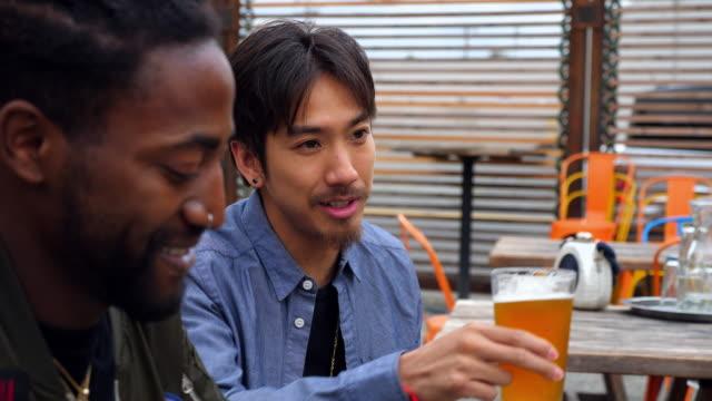 vídeos y material grabado en eventos de stock de ms smiling friends in discussion while sharing drinks at outdoor restaurant - 25 29 años