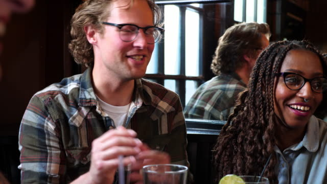 vidéos et rushes de ms smiling friends in discussion while sharing drinks in bar - lunettes de vue