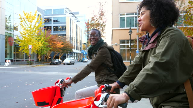 ms smiling friends in discussion while waiting at intersection during commute on electric bike share bikes - multiracial group stock videos & royalty-free footage