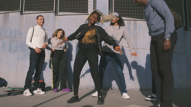 vídeos de stock e filmes b-roll de smiling friends looking at teenage girl dancing on sidewalk in city - cultura hip hop