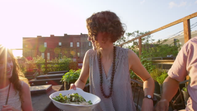 MS TS Smiling friends passing plate of food during dinner together in rooftop garden on summer evening