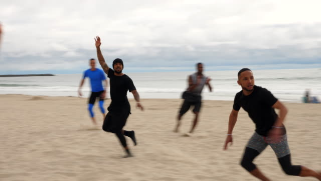 pan smiling friends playing touch football on beach on summer evening - touch football stock videos & royalty-free footage