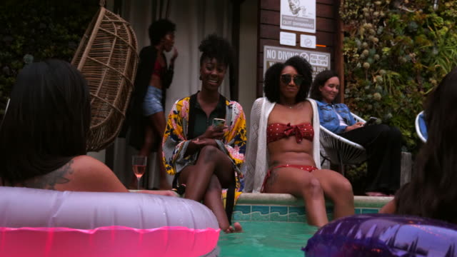 stockvideo's en b-roll-footage met ms smiling friends relaxing around hotel pool during party - zwembadrand