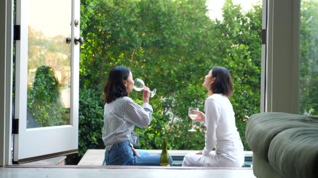 vídeos de stock e filmes b-roll de ms smiling friends sitting on deck overlooking backyard swimming pool sharing wine - amizade feminina