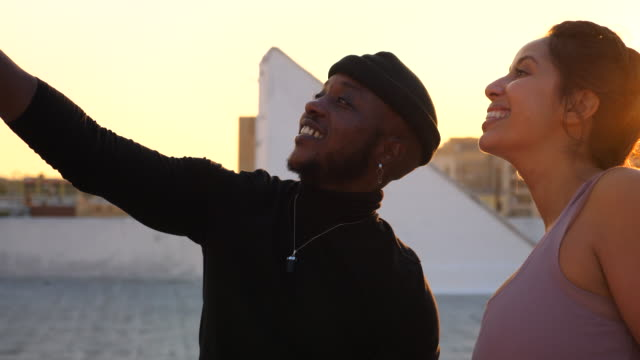 ms smiling friends taking a selfie after rooftop yoga class at sunset - roof stock videos & royalty-free footage