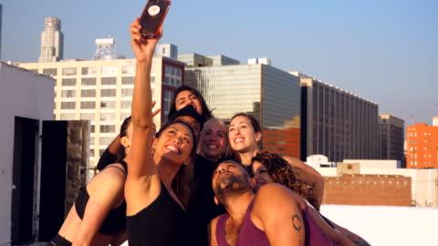 ms smiling friends taking group selfie after rooftop yoga class - mellanstor grupp av människor bildbanksvideor och videomaterial från bakom kulisserna