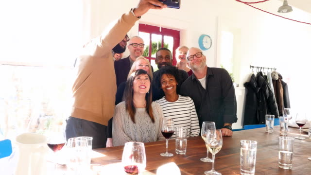 MS Smiling friends taking group selfie with smartphone after sharing holiday meal