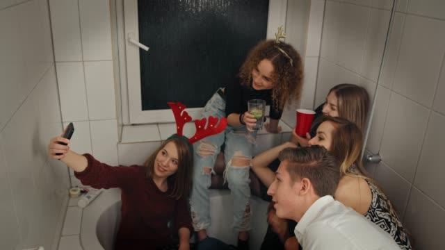 vidéos et rushes de sourire des amis prenant selfie sur téléphone dans la salle de bain - salle de bain