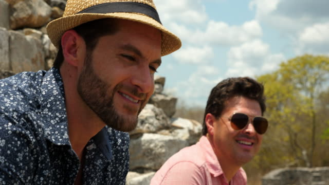 CU Smiling gay couple relaxing during trip to Mayapan ruins on vacation