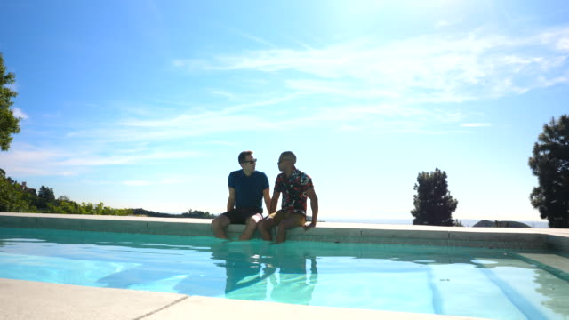 ws smiling gay couple relaxing with feet in pool at vacation rental - only mid adult men stock videos & royalty-free footage