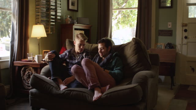 MS Smiling gay couple sitting on couch in home looking at digital tablet