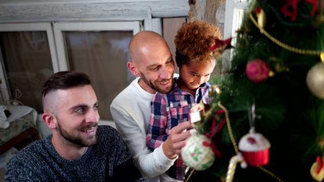 smiling gay family with a adopted child decorating a christmas tree at home - decoration stock videos & royalty-free footage