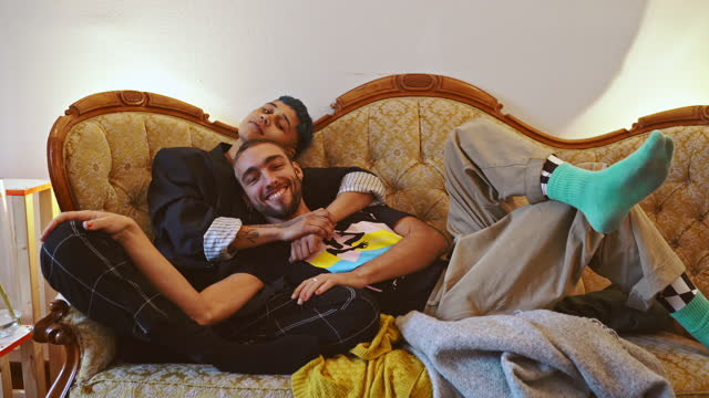 stockvideo's en b-roll-footage met smiling gay man relaxing with female friend on couch at home - etniciteit