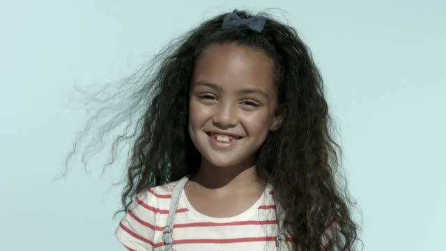 smiling girl against blue background on windy day - black hair stock videos & royalty-free footage