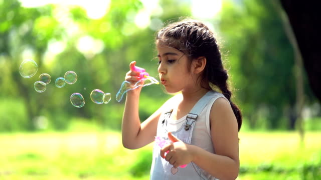 smiling girl blowing soap bubbles in summer park - childhood stock videos & royalty-free footage