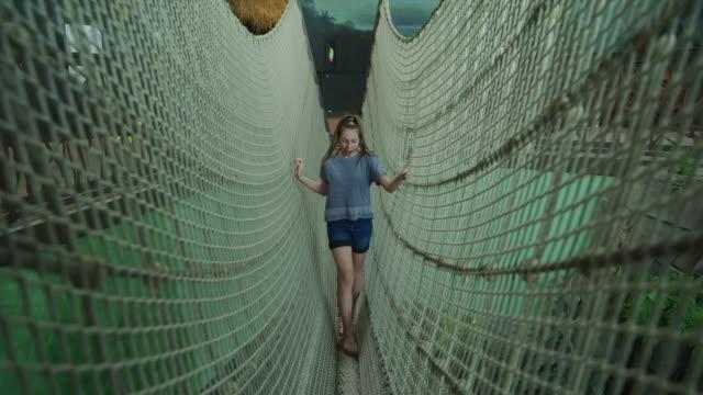 smiling girl crossing indoor rope bridge in aquarium / draper, utah, united states - three quarter length stock videos & royalty-free footage