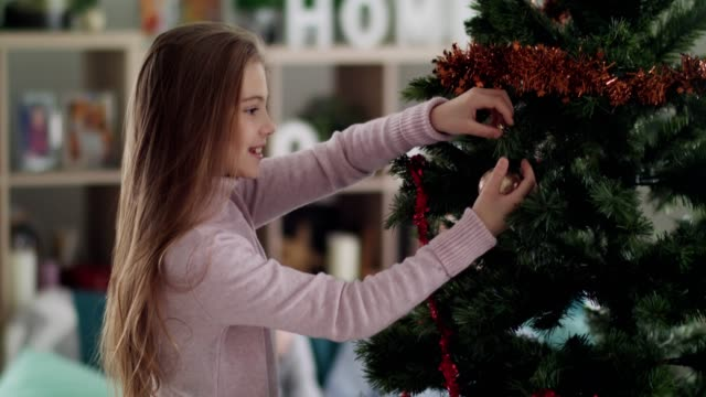 smiling girl decorating christmas tree - christmas tree stock videos & royalty-free footage