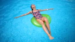 Smiling girl enjoying floating at the pool