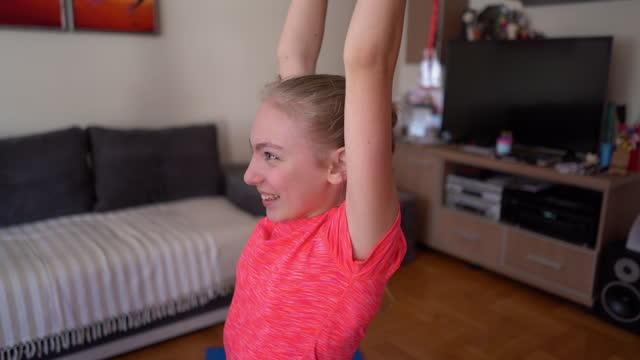 vídeos y material grabado en eventos de stock de chica sonriente haciendo ejercicio con banda de fitness en casa - sólo una adolescente