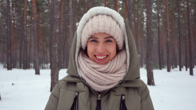 smiling girl folded arms while standing in the wintry forest on a snowy day - mitten stock videos and b-roll footage