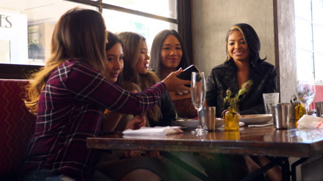 ms smiling girl friends taking selfie with smartphone during lunch party in restaurant - svart hår bildbanksvideor och videomaterial från bakom kulisserna