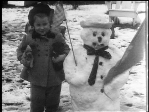 b/w 1944 portrait smiling girl holding puppies next to snowman with american flag / home movie - 1944 stock videos & royalty-free footage