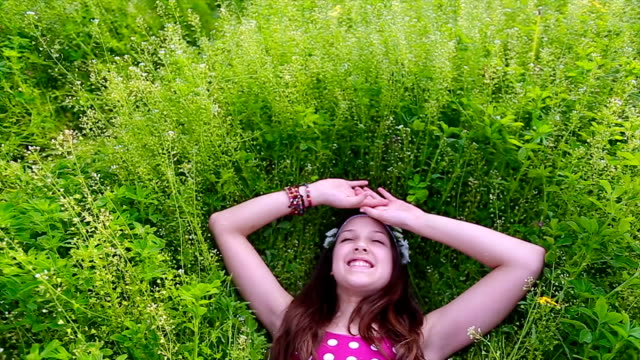 smiling girl laying in the meadow - reclining stock videos and b-roll footage