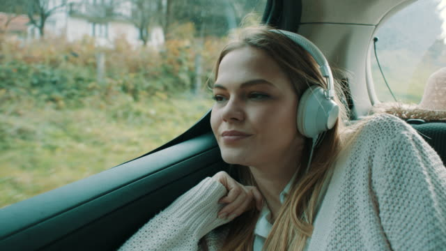 Smiling girl listening music on back seat of the car