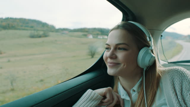 smiling girl listening music on back seat of the car - relax stock videos & royalty-free footage