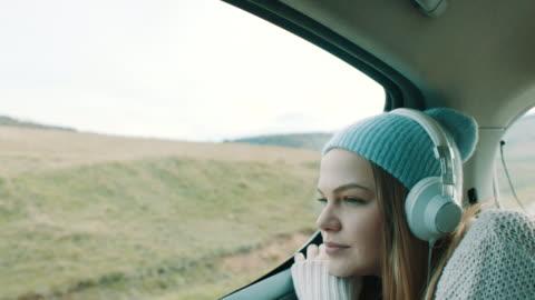 lächelnde mädchen musik hören auf dem rücksitz des autos - blondes haar stock-videos und b-roll-filmmaterial