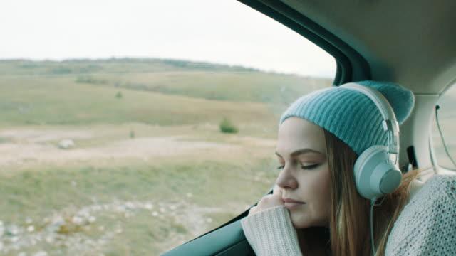 車の後部座席に笑みを浮かべて少女音楽を聴く