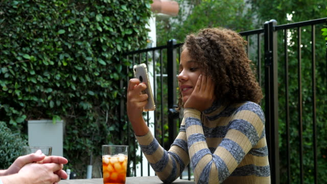 ms smiling girl looking at smart phone while sitting in backyard with father - pre adolescent child stock videos & royalty-free footage