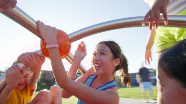 vidéos et rushes de ms smiling girl playing with friends on merry go round on playground - aire de jeux