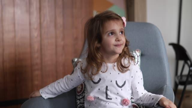 リビングルームでロッキングチェアに眠っている笑顔の女の子 - ジェンダーブレンド点の映像素材/bロール