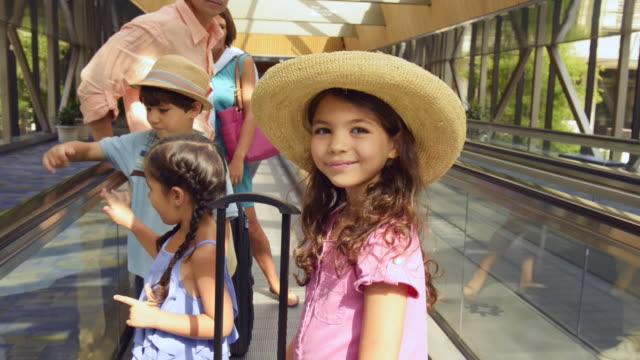 vídeos y material grabado en eventos de stock de smiling girl riding travolator at airport with family - suitcase