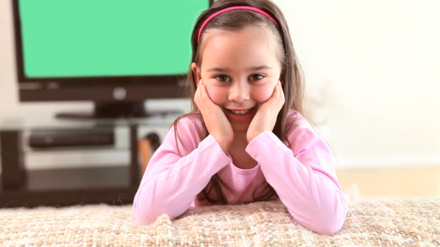 smiling girl sitting on a couch - hand am kinn stock-videos und b-roll-filmmaterial