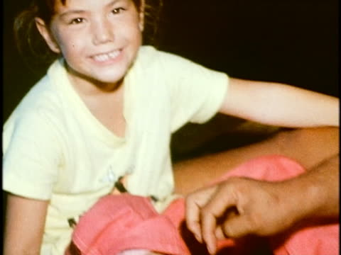 1975 montage zo ws smiling girl sitting on floor beside her father lacing up her roller skates at, 'rainbow rollerland' roller rink/ ws two girls lacing up their roller skates/ honolulu, oahu, hawaii islands, usa - anno 1975 video stock e b–roll