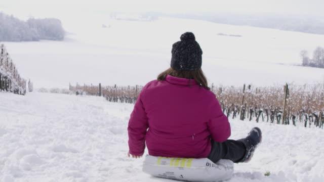 4K Smiling girl sledding in snowy vineyard, slow motion