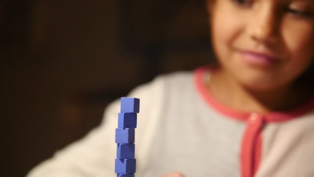 smiling girl stacking blue toy blocks in illuminated room at home - block shape stock videos & royalty-free footage