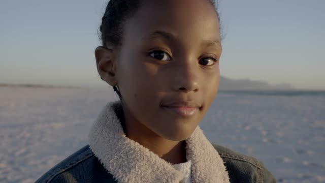 vidéos et rushes de smiling girl wearing denim jacket at beach during summer - environnement