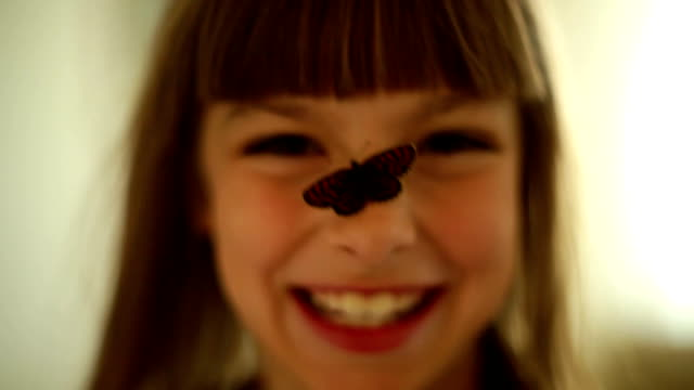Smiling girl with a butterfly on a nose