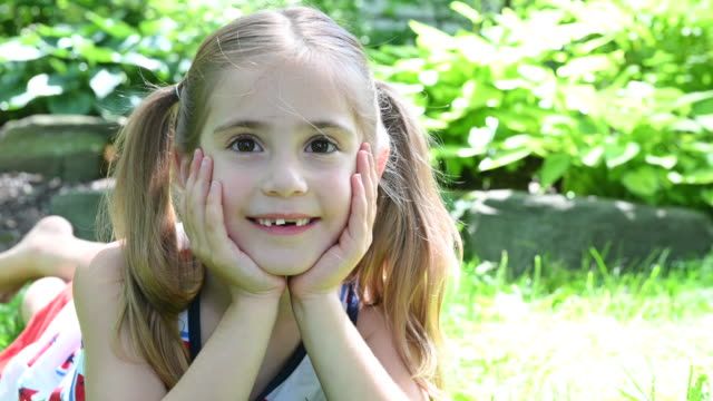 smiling girl with pigtails lying in grass - haarzopf stock-videos und b-roll-filmmaterial