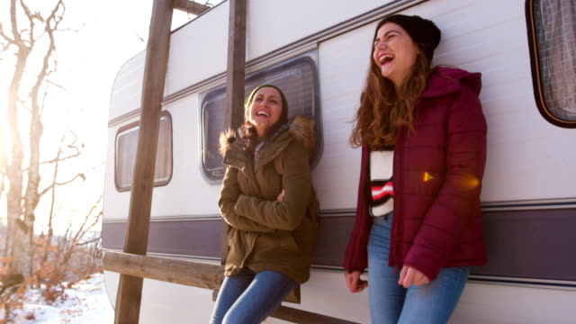 smiling girlfriends in front of a vintage camper trailer - camper trailer stock videos and b-roll footage