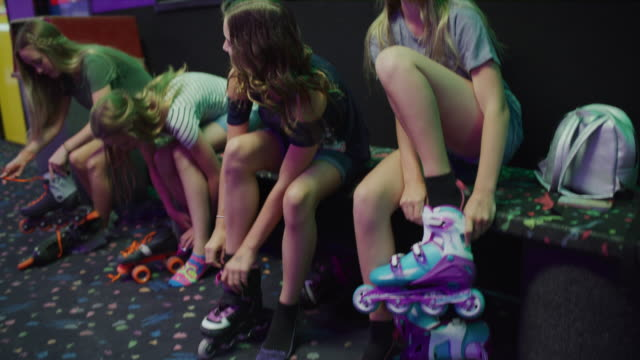 stockvideo's en b-roll-footage met smiling girls fastening roller skates at skating rink / orem, utah, united states - driekwartlengte