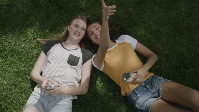 vídeos de stock e filmes b-roll de smiling girls laying on grass posing for cell phone selfie / provo, utah, united states - provo