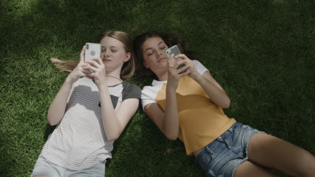 vídeos de stock, filmes e b-roll de smiling girls laying on grass using cell phones / provo, utah, united states - sending